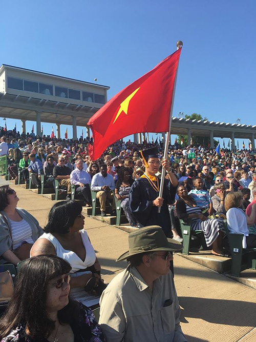 Quang Liêm đại diện sinh viên VN cầm cờ tiến đến lễ đài tốt nghiệp. Ảnh: Facebook của Quang Liêm
